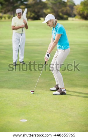 Full length of woman playing golf while standing by man