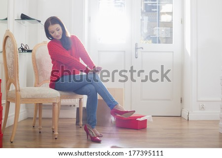 Full length of woman trying on footwear in store - stock photo
