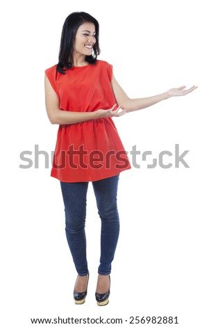 Full length of young asian woman standing in the studio with presenting hand gesture, isolated over white - stock photo