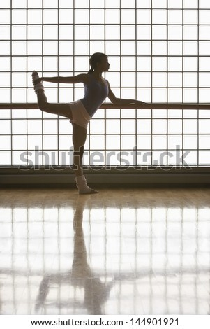Full length of young ballerina practicing at rehearsal - stock photo