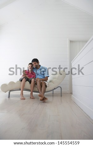Full length of young boy with father sitting on lounge chair at home - stock photo
