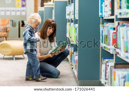 Full length of young boy with teacher selecting book from bookshelf in library - stock photo