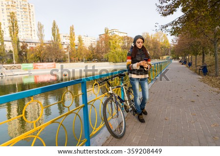 Full Length of Young Brunette Woman Standing with Cell Phone and Bicycle on Waterfront Promenade with Colorful Railing in Urban Park in Autumn