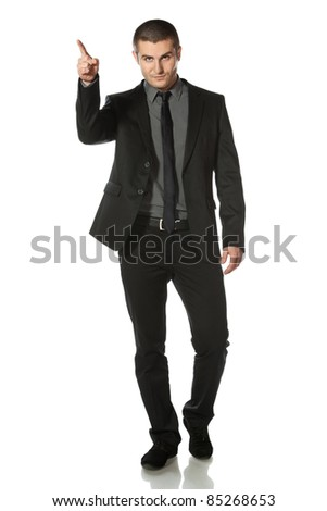 Full length of young business man in suit pointing at copy space over white background - stock photo