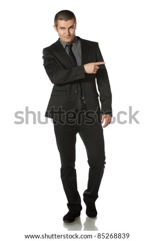 Full length of young business man in suit pointing at copy space over white background