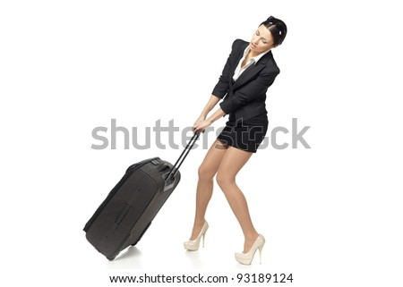 Full length of young business woman pulling the heavy travel bag, isolated on white background - stock photo