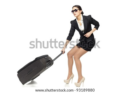 Full length of young business woman pulling the heavy travel bag, isolated on white background
