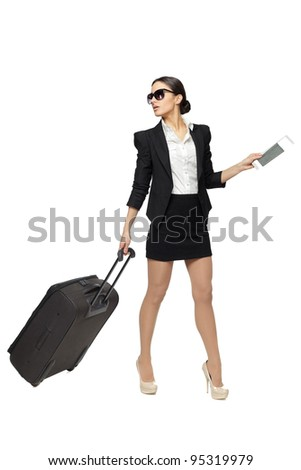 Full length of young business woman pulling the travel bag, isolated on white background - stock photo