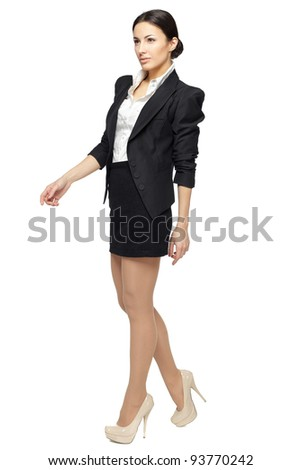 Full length of young business woman walking isolated on white - stock photo