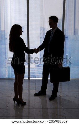 Full length of young businessman and businesswoman shaking hands in office - stock photo