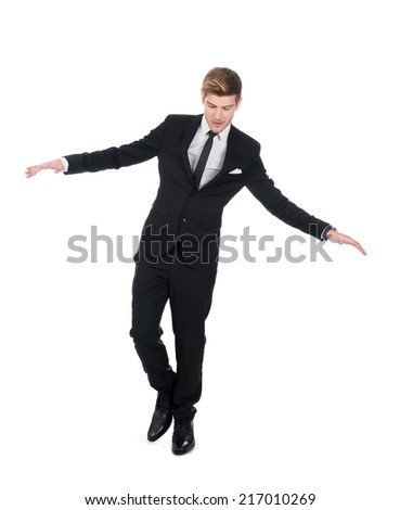 Full length of young businessman balancing over white background - stock photo