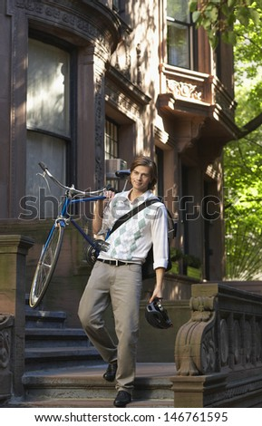 Full length of young businessman carrying bicycle while descending steps - stock photo