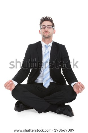 Full length of young businessman meditating over white background