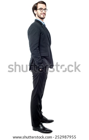 Full length of young businessman posing sideways - stock photo