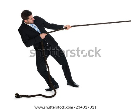 Full length of young businessman pulling rope over white background