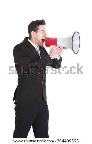 Full length of young businessman screaming into megaphone over white background - stock photo