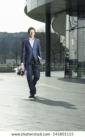 Full length of young businessman with bouquet and newspaper walking on street - stock photo