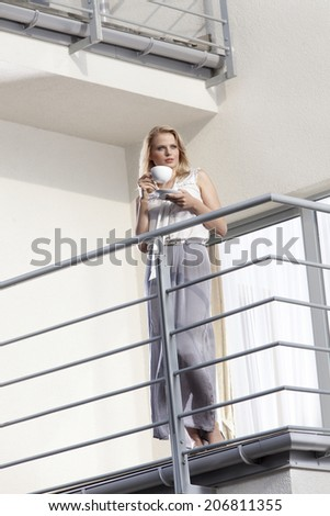 Full length of young businesswoman having coffee at hotel balcony - stock photo