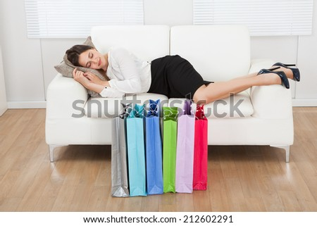 Full length of young businesswoman sleeping on sofa with shopping bags on floor at home - stock photo