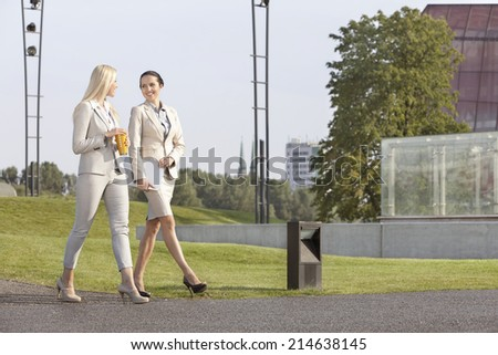 Full length of young businesswomen looking at each other while walking on street - stock photo