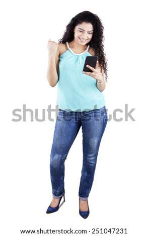 Full length of young casual indian woman standing in the studio while reading a message on the smartphone - stock photo