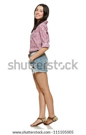 Full length of young charming female in shorts and floral shirt posing over white background