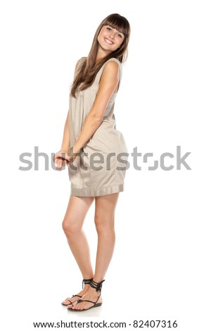 Full length of young charming female in summer dress posing over white background - stock photo