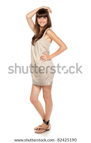 Full length of young charming female in summer dress posing over white background