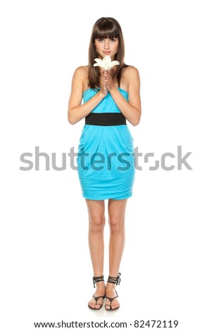 Full length of young charming female in sundress holding white lily over white background - stock photo
