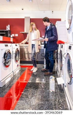 Full length of young couple choosing washing machine in hypermarket - stock photo