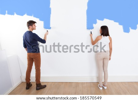 Full length of young couple painting new house - stock photo