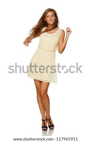 Full length of young elegant female in light yellow summer dress, over white background - stock photo