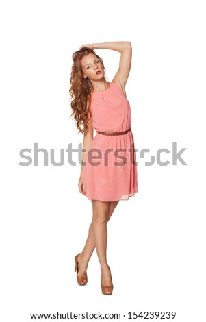 Full length of young elegant redheaded female in pink summer dress, over white background - stock photo