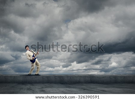 Full length of young excited businessman playing guitar on cloud background - stock photo