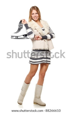 Full length of young female holding skates over white background - stock photo