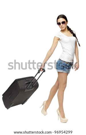 Full length of young female in casual pulling the travel bag, isolated on white background