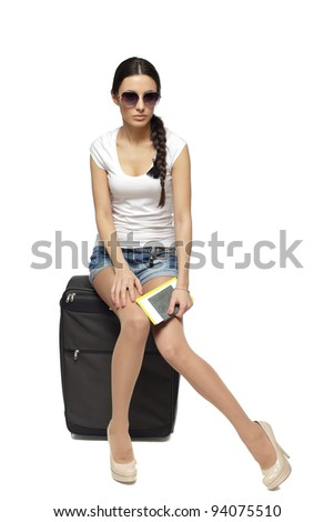 Full  length of young female in casual sitting on her black travel bag and holding the tickets with passport isolated on white background - stock photo