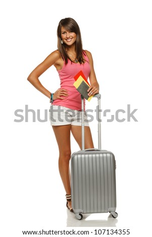 Full length of young female in casual standing with travel bag, holding passport and tickets, showing thumb up sign, isolated on white background - stock photo