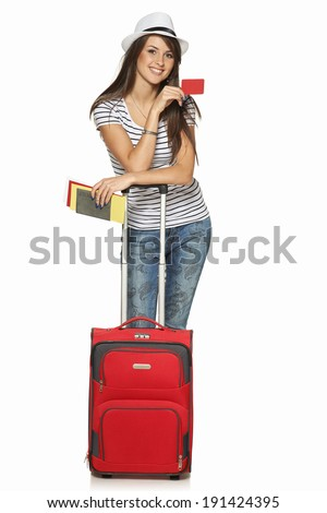 Full length of young female in casual standing with travel suitcase, holding passport and tickets, and showing blank credit card, isolated on white background - stock photo