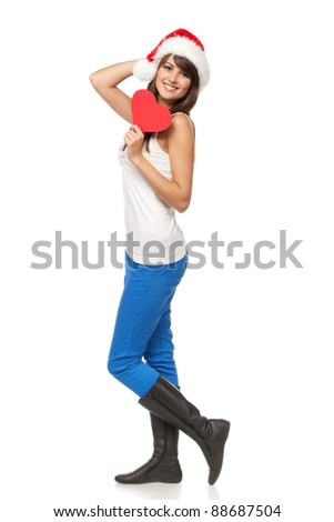Full length of young female in casual wearing Santa hat holding heart shape, isolated on white background - stock photo