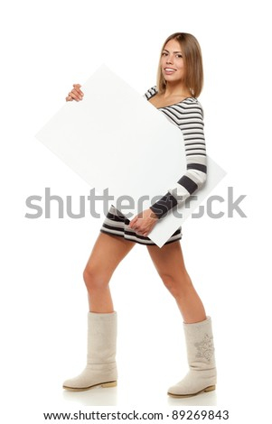 Full length of young female in winter dress and boots carrying a blank billboard sign, isolated on white background - stock photo