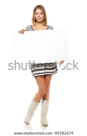 Full length of young female in winter dress and boots holding a blank billboard sign, isolated on white background - stock photo