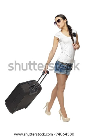 Full length of young female pulling the travel bag, isolated on white background