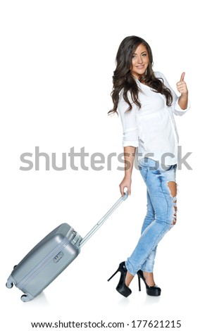 Full length of young female walking with the travel bag gesturing thumb up, isolated on white background - stock photo