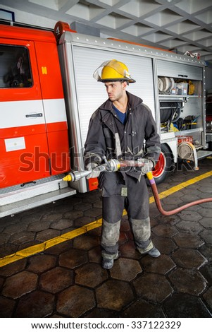 Full length of young fireman spraying water during training at fire station - stock photo