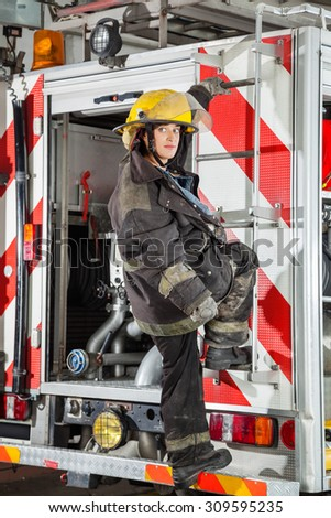 Full length of young firewoman looking away while standing on truck at fire station - stock photo