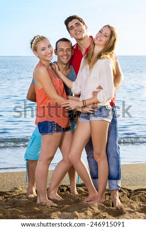 Full Length of Young Friends Enjoying at the Beach While Looking at the Camera. - stock photo