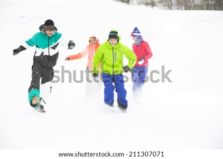 Full-length of young friends having fun in snow - stock photo