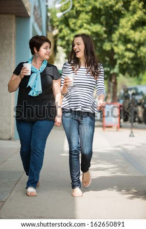 Full length of young friends with disposable coffee cups walking on pavement - stock photo