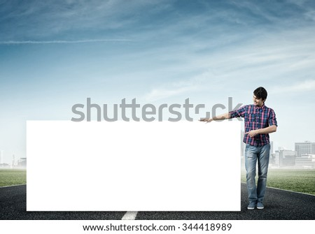 Full length of young handsome man with blank banner pointing on banner with finger - stock photo